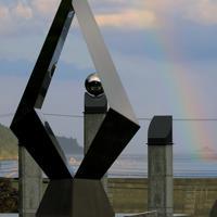 夕立の後、東日本大震災の犠牲者を悼むモニュメントの奧にでた虹=宮城県石巻市雄勝町で2019年8月25日午後5時18分、和田大典撮影