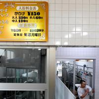 タイルの壁に残る、銭湯だったころの料金や営業時間を記した看板=大阪市東淀川区で、山田尚弘撮影