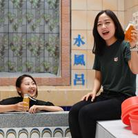 牛乳瓶に入ったビールを手に笑顔を見せる人たち=大阪市東淀川区で、山田尚弘撮影