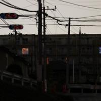 日没時間が過ぎ、信号の明かりも消え暗闇に包まれた住宅街。右奥の集合住宅街では懐中電灯の明かりと思われる光が見えた=千葉県市原市で2019年9月11日午後7時7分、玉城達郎撮影