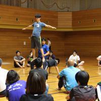 安全なサポート方法を説明しながら組み体操「サボテン」を実演する三宅良輔教授(立位の人の足を支えている男性)=神戸市長田区蓮池町の県立文化体育館で、生野由佳撮影