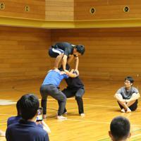 安全面を考慮し、下を2人にした「タワー」に挑戦する参加者=神戸市長田区蓮池町の県立文化体育館で、生野由佳撮影