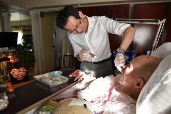 訪問診療で入れ歯の調整などをする五島朋幸さん=東京都渋谷区で、筆者撮影