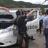 スマホのアプリを使った電気自動車の呼び出しの流れなど実証実験の一部が報道陣に公開された=北海道厚沢部町役場前で