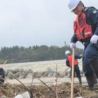 東日本大震災の行方不明者や遺留品を捜す亘理署員=宮城県山元町の磯浜漁港の海岸で