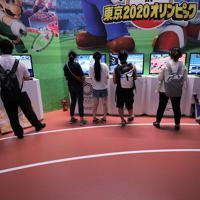 「東京ゲームショウ」で展示された、東京五輪をテーマにしたゲームで遊ぶ人たち=千葉市美浜区の幕張メッセで2019年9月12日、宮武祐希撮影
