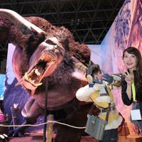 「東京ゲームショウ」のカプコンのブースで、ゲームのキャラクター像の前で記念撮影する人たち=千葉市美浜区の幕張メッセで2019年9月12日、宮武祐希撮影