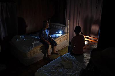 停電が続く自宅で懐中電灯をともして夜を過ごす夫婦。「片付けの疲れですぐ眠りに落ちても暑さで寝苦しい」と話した=千葉県館山市船形で2019年9月12日午後7時、北山夏帆撮影