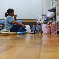 避難所でパンをかじりながら小型の携帯テレビを見る女性。「『何でこんな目に』と考えると涙が出る」と話す=千葉県館山市北条で2019年9月12日午後6時29分、北山夏帆撮影