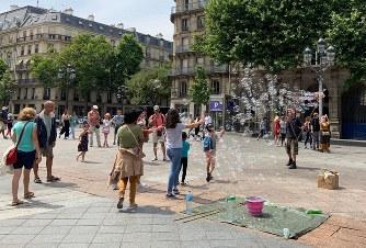 たくさんのしゃぼん玉を作り出す男性と喜ぶ観光客=パリ市内で筆者撮影
