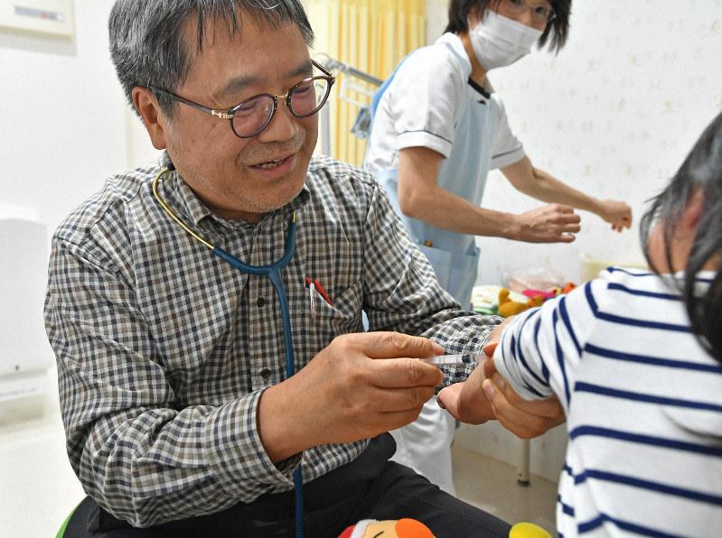 子供に予防接種をする医師