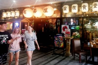 「深夜食堂」を前面に打ち出した日本料理店。店頭では日本版の映画が流れていた=上海市内で8月21日、赤間清広撮影