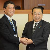 笑顔で握手を交わす田中和徳復興相(右)と村井嘉浩知事=宮城県庁で