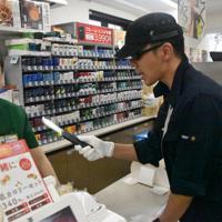 店員を大声で脅す強盗役の警察官(右)=横浜市中区で