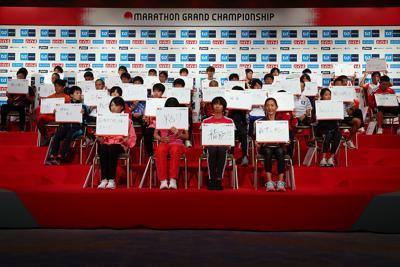 マラソングランドチャンピオンシップを前に、記者会見でボードを手に質問に答える選手たち=東京都新宿区で2019年9月13日、小川昌宏撮影