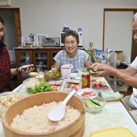 ラグビーW杯観戦に訪れる外国人を希望した袋井市民らが受け入れるホームステイ。練習のため訪れたフィリピンのメアリーさん(32歳・左)に手巻き寿司の食べ方を教える広岡英一さん(右・71)と妻のとみ江さん(64)。とみ江さんは「グローバル社会でいろいろな人と交流することは自分の可能性を広げられる。外国の方を家にお迎えするのは日常の良い刺激になります」と話す=静岡県袋井市で2019年8月24日午後5時48分、藤井達也撮影