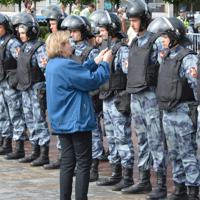 モスクワ市議選を巡るデモでは、一人の女性が抗議の意味を込め、警官隊の前まで進み写真を撮っていた=モスクワで2019年8月3日、大前仁撮影