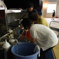 給水車の水をバケツに入れる市職員ら=千葉県南房総市白浜町の白浜コミュニティセンターで2019年9月12日午後8時28分、秋丸生帆撮影