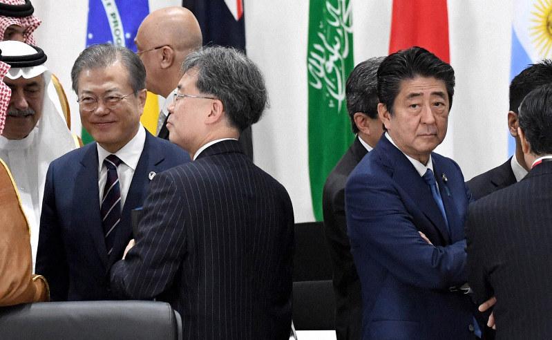G20サミットのセッション3開始前に韓国の文在寅大統領(左)と握手を交わした後、厳しい表情を見せる安倍晋三首相(右)=大阪市で2019年6月29日、竹内紀臣撮影