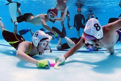 水中ホッケーをプレーする選手たち=広島県東広島市で2019年7月28日、猪飼健史撮影