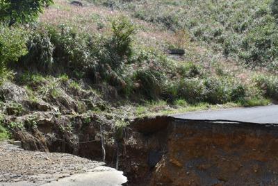 数回植林しても木が生えない「呪われた皆伐地」(奥)。昨夏の西日本豪雨では一部が崩れ、アスファルトの村道(手前)も崩壊した=岡山県西粟倉村で2018年9月、寺田剛撮影