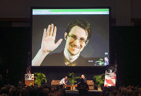 In this Feb. 14, 2015, file photo, Edward Snowden appears on a live video feed broadcast from Moscow at an event sponsored by ACLU Hawaii in Honolulu. (AP Photo/Marco Garcia)