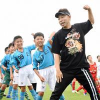 試合前に体操をするEXILEのUSAさん(右)と選手たち=愛媛県今治市高橋ふれあいの丘のありがとうサービス.夢スタジアムで、中川祐一撮影