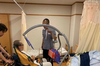 車いすからベッドへ移動=2019年8月、広島県廿日市市のふれあいライフ原で(鎌田さん提供)