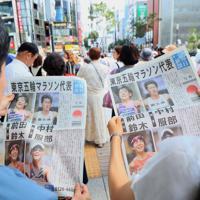 東京五輪マラソン代表内定の号外を手にする人たち=東京都中央区で2019年9月15日午後1時8分、玉城達郎撮影