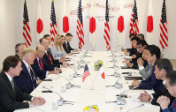 In this June 28, 2019 file photo, Prime Minister Shinzo Abe, third from right, and U.S. President Donald Trump, second from left, and their teams sit down for talks in Osaka's Suminoe Ward. (Pool photo)