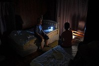 In this Sept. 12, 2019 file photo, a married couple use torches to light their room during an ongoing blackout following Typhoon Faxai, in Tateyama, Chiba Prefecture. (Mainichi/Kaho Kitayama)