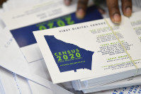 In this Aug. 13, 2019, file photo, a worker gets ready to pass out instructions in how fill out the 2020 census during a town hall meeting in Lithonia, Ga. (AP Photo/John Amis)