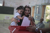 A voter casts her ballot as she carries her daughter inside a polling station during the first round of the presidential election, in Tunis, Tunisia, on Sept. 15, 2019. (AP Photo/Mosa'ab Elshamy)