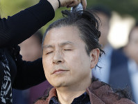 Hwang Kyo-ahn, the main opposition Liberty Korea Party chairman, has his head shaved in Seoul, South Korea, on Sept. 16, 2019. The leader of South Korea's biggest opposition party has become the latest politician to shave their heads to protest President Moon Jae-in's appointment of a key political ally as justice minister despite allegations of academic fraud and financial crimes surrounding his family. (AP Photo/Lee Jin-man)