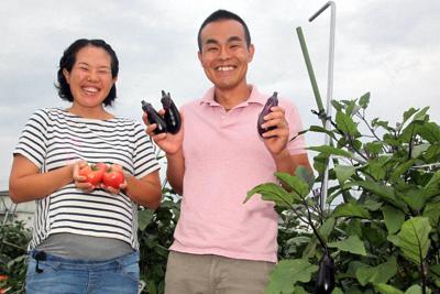 「よしよし畑」で収穫された野菜を手に、笑顔をみせる久世継義さん、志穂さん夫妻=兵庫県加西市下宮木町で、高尾具成撮影