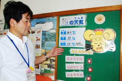 暑さ指数などについて説明する大津市立中央小学校の高岸均校長=同市島の関で12日、渡辺諒撮影