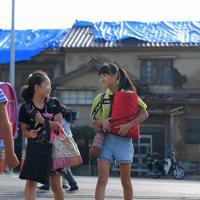 台風15号による被災後、休校が続いていた小学校が再開し、、荷物を抱えて友人らと登校する児童たち=千葉県南房総市の市立富浦小で2019年9月17日午前7時46分、手塚耕一郎撮影