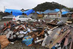 台風15号による被災から1週間が経ち、屋根のブルーシートが目立つ住宅と、空き地に集められたがれきの山=千葉県館山市布良で2019年9月16日午後2時32分、手塚耕一郎撮影