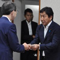 福島県庁を訪問し、内堀雅雄知事(左)に名刺を渡す菅原一秀経産相