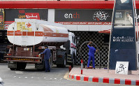 Workers refuel the tank at a gas station in Jiddah, Saudi Arabia, on Sept. 17, 2019. (AP Photo/Amr Nabil)