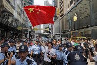 A pro-China supporter is escorted out of a shopping mall by police while waving a Chinese national flag in Hong Kong, on Sept. 18, 2019. (AP Photo/Kin Cheung)