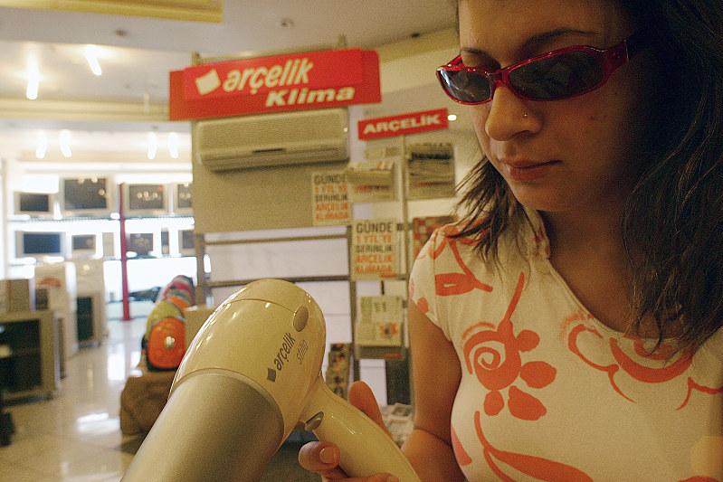 アルチェリクの家電製品を手に取る女性(Bloomberg)