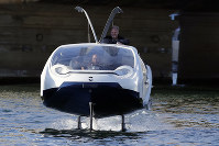 SeaBubbles co-founder Sweden's Anders Bringdal stands onboard a SeaBubble, on Sept. 18, 2019 in Paris. (AP Photo/Francois Mori)