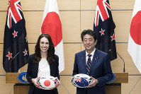 New Zealand's Prime Minister Jacinda Ardern, left, and Japan's Prime Minister Shinzo Abe hold rugby balls after a joint press conference following a meeting at the prime minister's office in Tokyo, on Sept. 19, 2019. (Tomohiro Ohsumi/Pool Photo via AP)