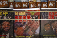 In this July 4, 2019 file photo, magazines with a front cover featuring Chinese President Xi Jinping and U.S. President Donald Trump on trade war are seen on sale at a roadside bookstand in Hong Kong. (AP Photo/Andy Wong)