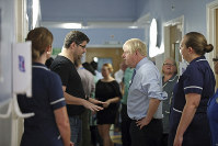 The father of a young patient, who is being treated in the Acorn children's ward, talks to Britain's Prime Minister Boris Johnson during his visit to Whipps Cross University Hospital in Leytonstone, east London, on Sept. 18, 2019. (Yui Mok/Pool via AP)