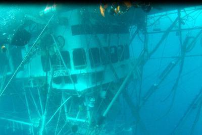 転覆した「第65慶栄丸」の海中写真。船は逆さになり、周辺には網や照明などの設備が絡まっていた=第1管区海上保安本部提供