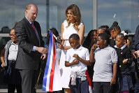 First lady Melania Trump, center, and Department of Interior assistant secretary Rob Wallace, left, participate in a ribbon-cutting ceremony with students from Amidon-Bowen Elementary School in Washington to re-open the Washington Monument, on Sept. 19, 2019, in Washington. (AP Photo/Patrick Semansky)