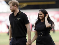 In this June 29, 2019 file photo, Britain's Prince Harry, left, and Meghan, Duchess of Sussex, walk off the field before a baseball game in London. (AP Photo/Tim Ireland)