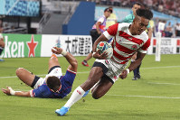 Japan's Kotaro Matsushima runs to scoring a try during the Rugby World Cup Pool A game at Tokyo Stadium between Russia and Japan in Tokyo, on Sept. 20, 2019. (AP Photo/Eugene Hoshiko)